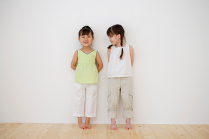 白い壁の前に立つ女の子2人の写真素材 [FYI02013100]