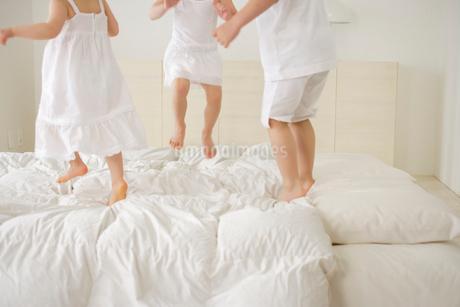 ベッドの上で遊ぶ女の子と男の子の写真素材 [FYI02013257]
