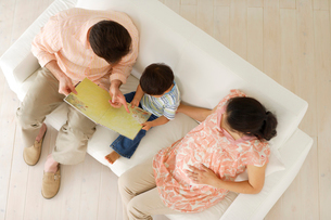 ソファで絵本を読む親子の写真素材 [FYI02013295]