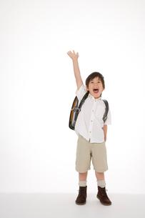 右手を挙げるランドセルを背負った男の子の写真素材 [FYI02013560]
