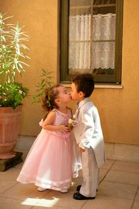 キスするタキシード姿の男の子とドレスを着た女の子の写真素材 [FYI02013611]