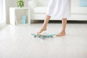 体重計に乗る女性の足元の写真素材 [FYI02013945]