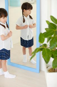 鏡の前で着替えをする女の子の写真素材 [FYI02013992]