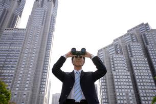 双眼鏡をのぞくスーツ姿の男性の写真素材 [FYI02014036]