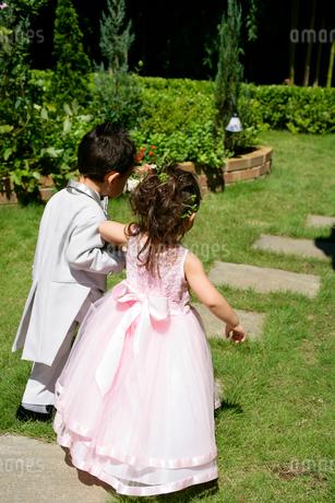 タキシード姿の男の子とドレスを着た女の子の後姿の写真素材 [FYI02014057]