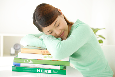 本を積み上げて眠る女性の写真素材 [FYI02014217]