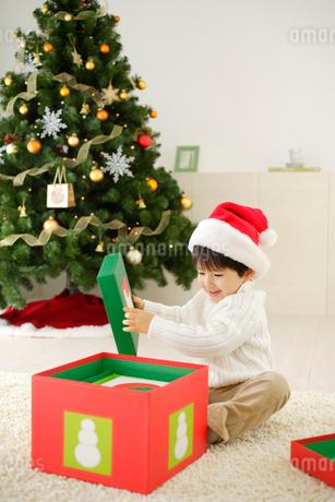プレゼントの箱を開ける男の子の写真素材 [FYI02014480]