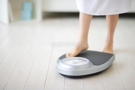 体重計に乗る女性の足元の写真素材 [FYI02014706]