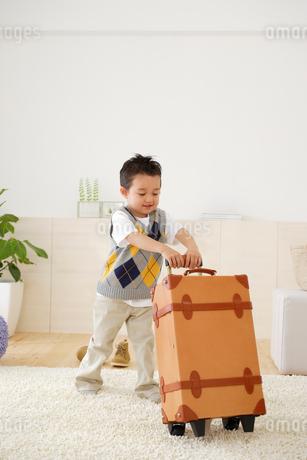 スーツケースを押す男の子の写真素材 [FYI02014825]