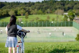 テニスコートを見つめる女子高生の後姿の写真素材 [FYI02015493]