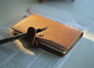 英字新聞とシステム手帳と万年筆の写真素材 [FYI02015800]