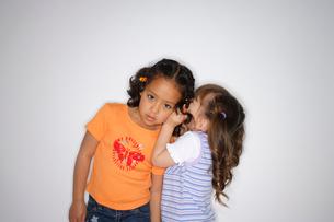 ないしょ話をする女の子2人の写真素材 [FYI02016474]