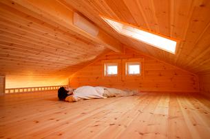 ログハウスのロフトで昼寝する男性の写真素材 [FYI02016539]