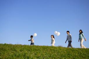 青空の下 散歩する家族の写真素材 [FYI02016618]