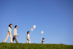 青空の下 散歩する家族の写真素材 [FYI02016648]