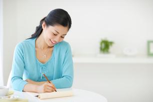 紅茶を飲みながら手紙を書く女性の写真素材 [FYI02016881]