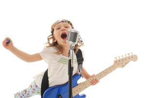 エレキギターを掻き鳴らす女の子の写真素材 [FYI02017096]