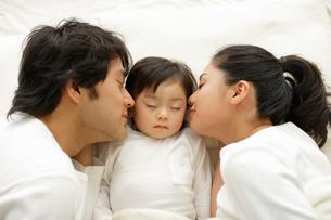 ベッドで横になる親子の写真素材 [FYI02017421]
