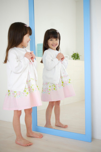 鏡の前でボタンをかける女の子の写真素材 [FYI02017446]