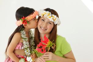 フラダンスの衣装を着てお花を持っている親子の写真素材 [FYI02017634]