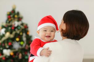 赤ちゃんサンタを抱くママとクリスマスツリーの写真素材 [FYI02017832]