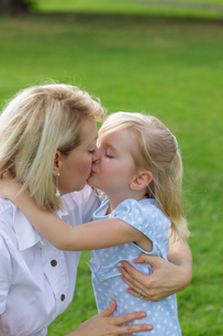 緑の中でキスをする女の子とお母さんの写真素材 [FYI02017844]