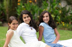 芝生の上に座る外国人姉妹の写真素材 [FYI02017969]
