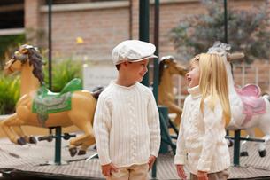 メリーゴーランドの前に立つ外国人の男の子と女の子の写真素材 [FYI02018101]