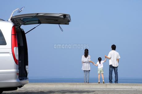 手を繋いで海を見つめる親子の写真素材 [FYI02018140]