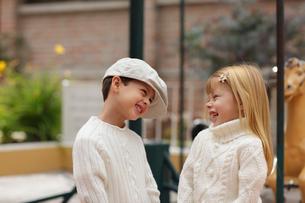メリーゴーランドの前に立つ外国人の男の子と女の子の写真素材 [FYI02018156]