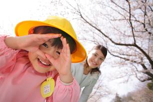カメラを覗き込むスーツ姿のお母さんと幼稚園児の女の子の写真素材 [FYI02018221]