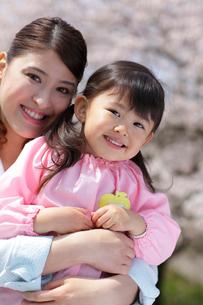 桜の前で園服の女の子を抱きしめるスーツ姿のお母さんの写真素材 [FYI02018238]