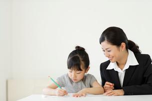 先生に勉強を教わる女の子の写真素材 [FYI02018258]