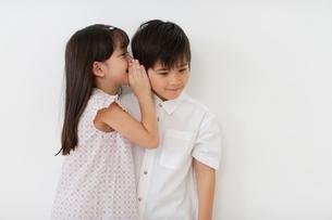 内緒話をするハーフの男の子と女の子の写真素材 [FYI02018273]