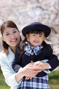 桜の前で制服姿の女の子を抱きしめるスーツ姿のお母さんの写真素材 [FYI02018281]