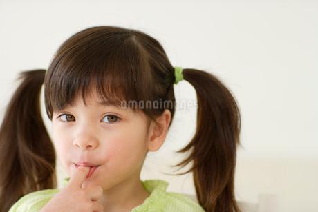 クリームをなめる女の子の写真素材 [FYI02018343]