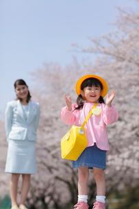 桜をバックに微笑むスーツ姿のお母さんと幼稚園児の女の子の写真素材 [FYI02018415]