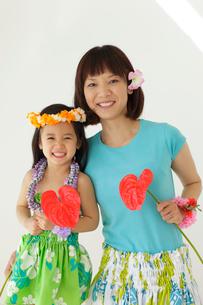フラダンスの衣装を着てお花を持っている親子の写真素材 [FYI02018487]