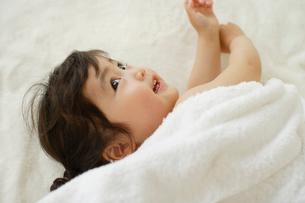 ブランケットの上でまっ白なタオルに包まれる女の子の写真素材 [FYI02018659]
