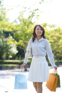 たくさんの紙袋を持って歩いている若い女性の写真素材 [FYI02018689]