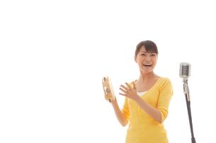 タンバリンを叩きながら歌う女性の写真素材 [FYI02018744]