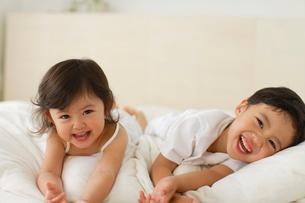ベッドの上でゴロゴロする兄妹の写真素材 [FYI02018807]
