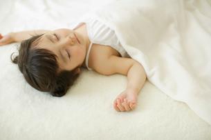 白いブランケットの上で眠る幼い女の子の写真素材 [FYI02018914]