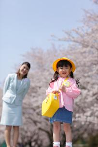 桜をバックに微笑むスーツ姿のお母さんと幼稚園児の女の子の写真素材 [FYI02018929]
