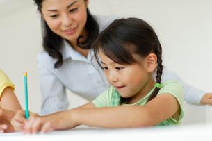 勉強する女の子たちと教える先生の写真素材 [FYI02018939]