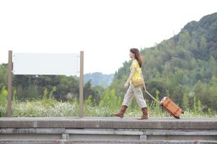 スーツケースを引いてホームを歩く一人旅の女性の写真素材 [FYI02019042]