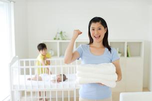 タオルを持つお母さんと赤ちゃんをあやす男の子の写真素材 [FYI02019046]