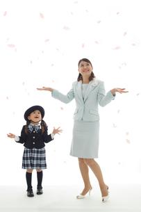 桜の花びらを見上げる制服姿の幼稚園児とお母さんの写真素材 [FYI02019056]