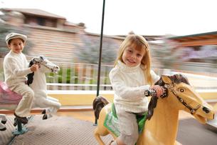 メリーゴーランドに乗る外国人の男の子と女の子の写真素材 [FYI02019111]