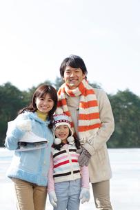 スケートリンクの前で寄り添う親子の写真素材 [FYI02019248]